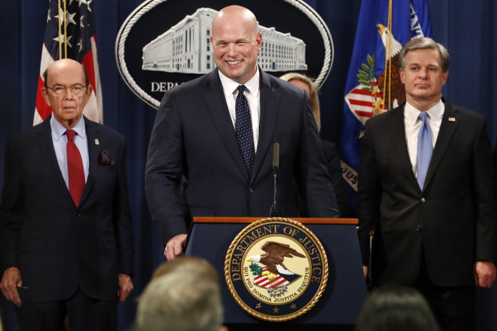 Acting Attorney General Matt Whitaker, center, smiles at a question from a reporter after an announcement of an indictment of Chinese telecommunications companies including Huawei, on violations including bank and wire fraud, Monday, Jan. 28, 2019, at the Justice Department in Washington. At left is Commerce Secretary Wilbur Ross, and FBI Director Christopher Wray, at right. (AP Photo/Jacquelyn Martin)