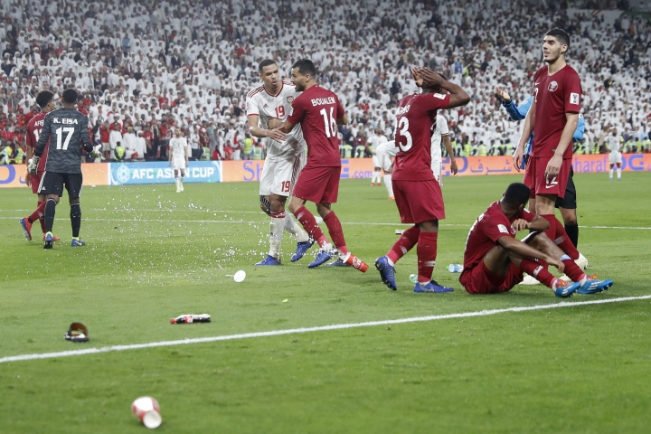 Qatar's defender Salem Al Hajri, right bottom, lies on the pitch after shoes and bottles where thrown in by United Arab Emirates fans during the AFC Asian Cup semifinal soccer match between United Arab Emirates and Qatar at Mohammed Bin Zayed Stadium in Abu Dhabi, United Arab Emirates, Tuesday, Jan. 29, 2019. (AP Photo/Hassan Ammar)