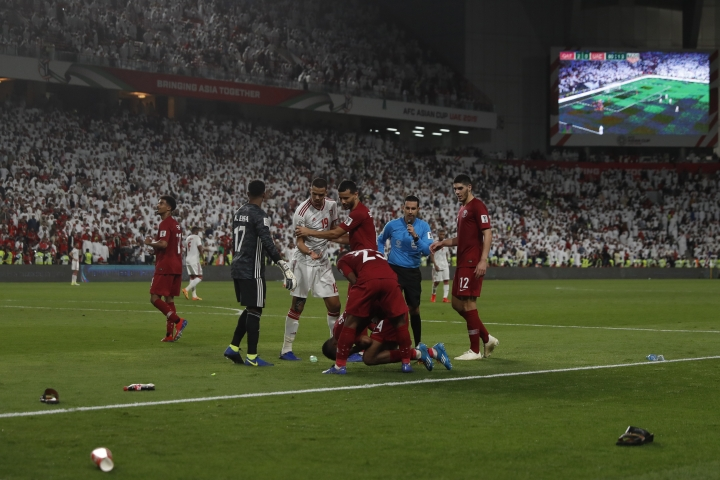 Qatar's defender Salem Al Hajri, lies on the pitch after shoes and bottles where thrown in by United Arab Emirates fans during the AFC Asian Cup semifinal soccer match between United Arab Emirates and Qatar at Mohammed Bin Zayed Stadium in Abu Dhabi, United Arab Emirates, Tuesday, Jan. 29, 2019. (AP Photo/Hassan Ammar)