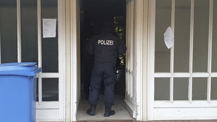 CORRECTS NAME OF LOCATION A police officer stand in an entrance of an apartment building during a raid in the village Meldorf, Germany, Jan. 30, 2019. German authorities arrested three suspected Islamic extremist Iraqi men in the norther German costal region, on allegations they were planning a bombing. (Karsten Schroeder/dpa via AP)