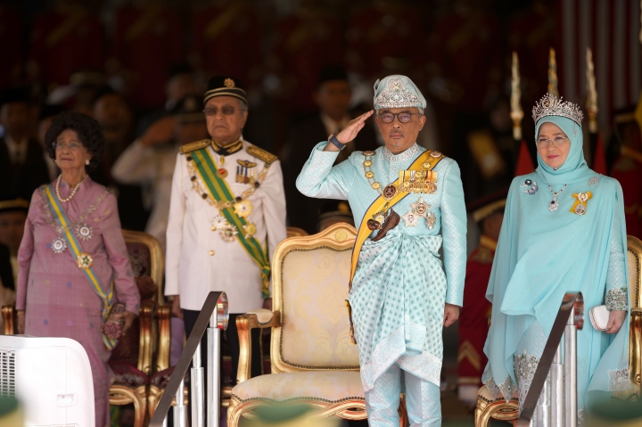 Malaysia's King Sultan Abdullah Sultan Ahmad Shah salutes next to Queen Tunku Azizah Aminah Maimunah, right, Prime Minister Mahathir Mohamad, second from left, and his wife Siti Hasmah during the king's welcome ceremony at Parliament House in Kuala Lumpur, Malaysia, Thursday, Jan. 31, 2019. Sultan Abdullah, ruler of central Pahang state, was named Malaysia's new king, replacing Sultan Muhammad V who abdicated unexpectedly after just two years on the throne. (AP Photo/Yam G-Jun)