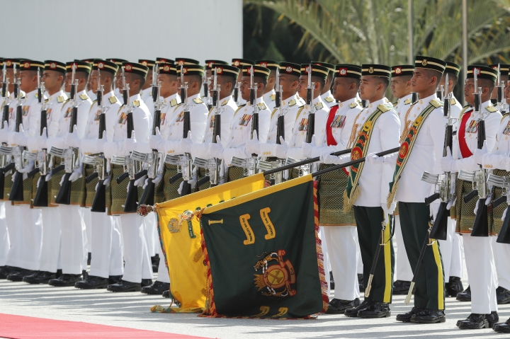 Malaysian Royal Guard salute during a welcome ceremony for King Sultan Abdullah Sultan Ahmad Shah at Parliament House in Kuala Lumpur, Malaysia, Thursday, Jan. 31, 2019. Sultan Abdullah, ruler of central Pahang state, was named Malaysia's new king, replacing Sultan Muhammad V who abdicated unexpectedly after just two years on the throne. (AP Photo/Vincent Thian)