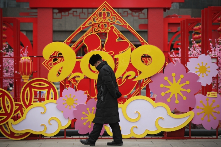 A man walks by a Lunar New Year decoration on display outside a commercial office building in Beijing, Thursday, Jan. 31, 2019. China's manufacturing improved in January, a survey showed Thursday, but forecasters said activity remains sluggish as Beijing tries to resolve a tariff battle with Washington. (AP Photo/Andy Wong)