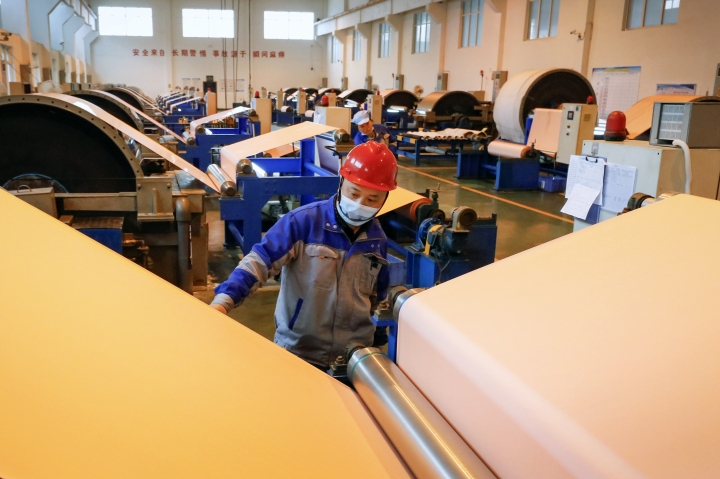 In this Jan. 19, 2019, photo, worker checks on a copper foil machines at a factory in Jiujiang in central China's Jiangxi province. An official measure of China's manufacturing improved in January but forecasters say economic activity is sluggish as Chinese leaders try to resolve a tariff battle with Washington. (Chinatopix via AP)