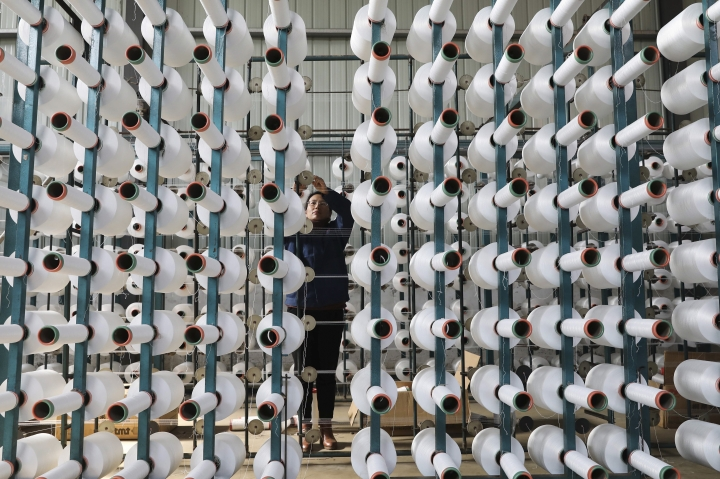 In this Jan. 21, 2019, photo, a worker adjusts a cotton string roll at a textile factory in Hangzhou in east China's Zhejiang province. An official measure of China's manufacturing improved in January but forecasters say economic activity is sluggish as Chinese leaders try to resolve a tariff battle with Washington. (Chinatopix via AP)