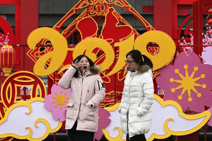 A woman yawns as she and her friend walk by a Lunar New Year decoration on display outside a commercial office building in Beijing, Thursday, Jan. 31, 2019. China's manufacturing improved in January, a survey showed Thursday, but forecasters said activity remains sluggish as Beijing tries to resolve a tariff battle with Washington. (AP Photo/Andy Wong)