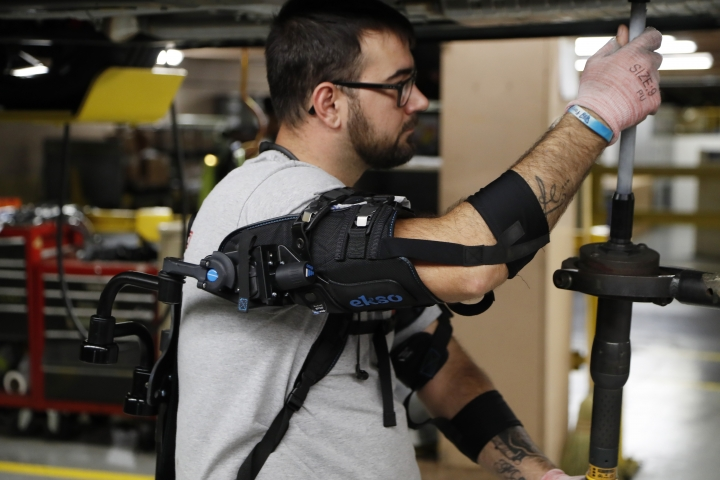 In this Sept. 18, 2018, photo Ford assembly line worker Nicholas Gotts, wearing a new wearable technology called an EksoVest, works on a vehicle in Flat Rock, Mich. The wearable device, that the automaker will be providing plants around the world, provides lift assistance from 5 to 15 pounds per arm. (AP Photo/Carlos Osorio)