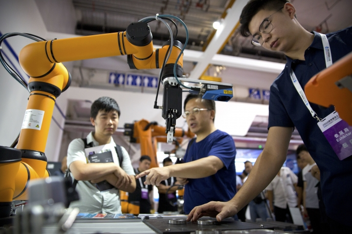 FILE - In this Aug. 18, 2018, file photo, visitors look at a manufacturing robot from Chinese robot maker Aubo Robotics at the World Robot Conference in Beijing, China. China's government has appealed to Washington to accept its industrial progress after U.S. intelligence officials said Beijing helps to steal and copy foreign technologies. (AP Photo/Mark Schiefelbein, File)