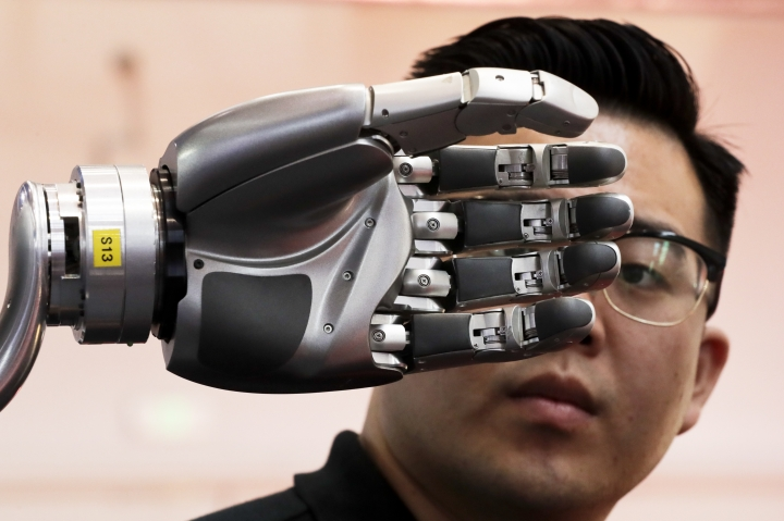 FILE - In this Aug. 23, 2017, file photo, a visitor looks at a robotic hand powered by Kinfinity Glove, developed by the German Aerospace Center, on display at the World Robot Conference at the Yichuang International Conference and Exhibition Centre in Beijing. China's government has appealed to Washington to accept its industrial progress after U.S. intelligence officials said Beijing helps to steal and copy foreign technologies. (AP Photo/Andy Wong)