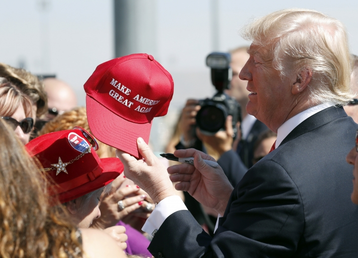 """FILE- In this Aug. 23, 2017 file photo, President Donald Trump hands a signed """"Make America Great Again,"""" hat back to a supporter in Reno, Nev. An award-winning cookbook author and California restaurant owner says anyone wearing a red """"Make America Great Again"""" baseball cap will be refused service at his restaurant. J. Kenji Lopez-Alt is a chef-partner of the Wursthall restaurant in San Mateo and says in a tweet Sunday, Jan. 27, 2019, that he views the hats as symbols of intolerance and hate. (AP Photo/Alex Brandon, File)"""