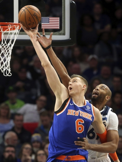 FILE - In this Jan. 12, 2018, file photo, New York Knicks' Kristaps Porzingis, left, of Latvia, outreaches Minnesota Timberwolves' Taj Gibson as he lays up the ball in the first half of an NBA basketball game in Minneapolis. The Knicks agree to trade injured star Kristaps Porzingis to Dallas Mavericks on Thursday, Jan. 31, 2019. (AP Photo/Jim Mone, File)