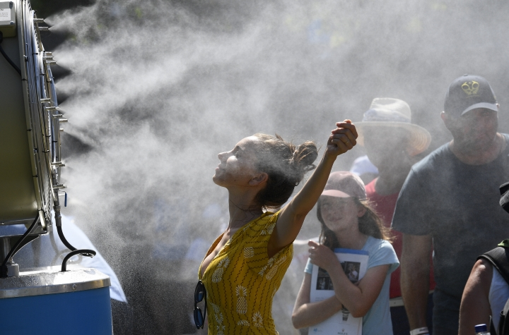 In this Jan. 14, 2019, file photo, spectators cool themselves down with a water mist fan during play on day one at the Australian Open tennis championships in Melbourne, Australia. Australia has sweltered through its hottest month on record in January and the summer of extremes continues with wildfires razing the drought-parched south while expanses of the tropical north are flooded. Australia's Bureau of Meteorology confirmed the record heat during January as parts of the northern hemisphere have had record cold. (AP Photo/Andy Brownbill, File)