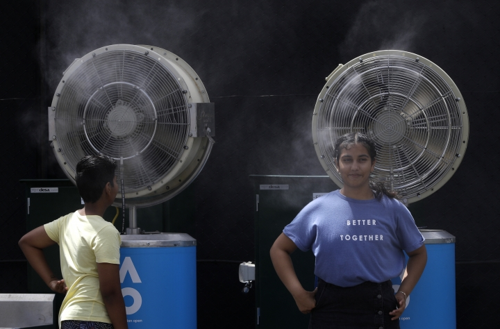 FILE - In this Friday, Jan. 25, 2019, file photo, spectators cool themselves down by water-cooling fans at the Australian Open tennis championships in Melbourne, Australia. Australia has sweltered through its hottest month on record in January and the summer of extremes continues with wildfires razing the drought-parched south while expanses of the tropical north are flooded. Australia's Bureau of Meteorology confirmed the record heat during January as parts of the northern hemisphere have had record cold. (AP Photo/Kin Cheung, File)