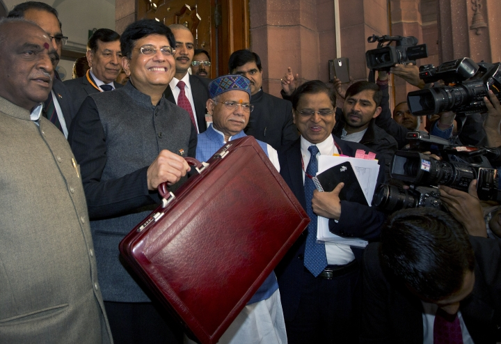 Interim Finance Minister Piyush Goyal, center, holds a briefcase containing federal budget documents with Junior Finance minsters Shiv Pratap Shukla, center right, and Pon Radhakrishnan, left, pose for the media on their arrival at the parliament house in New Delhi, India, Friday, Feb. 1, 2019. The Bharatiya Janata Party-led National Democratic Alliance government will present its last budget of five-year tenure on Feb. 1 as it prepares to face tens of millions of voters in national elections to be held by May. (AP Photo/Manish Swarup)