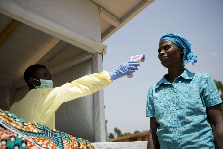 A patient has her temperature taken at the entrance to a health centre, as part of a triage system and Ebola prevention campaign that has been set up by the Swiss NGO Medair, in Mbau, near Beni in North Kivu province, in Congo Friday, Feb. 1, 2019. The deadly Ebola outbreak in eastern Congo marked six months on Friday. (Kate Holt/Medair via AP)