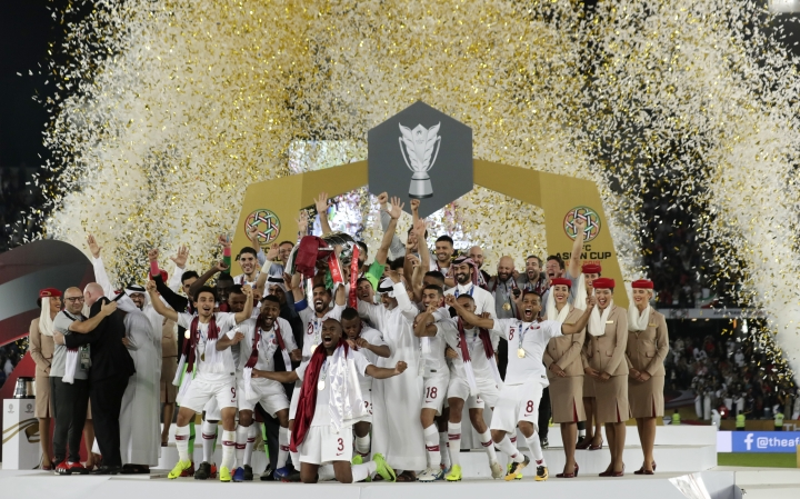 Qatar's forward Hasan Al Haydos, center, lifts the trophy for the winners of the AFC Asian Cup final match between Japan and Qatar in Zayed Sport City in Abu Dhabi, United Arab Emirates, Friday, Feb. 1, 2019. (AP Photo/Hassan Ammar)