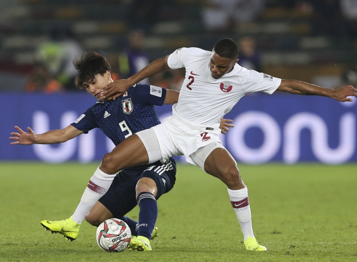 Japan's forward Takumi Minamino , left, and Qatar's defender Pedro Miguel Correia fight for the ball during the AFC Asian Cup final match between Japan and Qatar in Zayed Sport City in Abu Dhabi, United Arab Emirates, Friday, Feb. 1, 2019. (AP Photo/Kamran Jebreili)