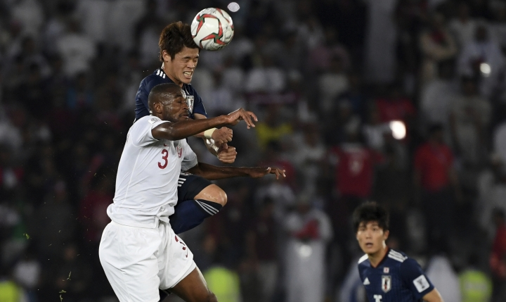 Qatar's defender Abdelkarim Hassan, front, challenges Japan's defender Hiroki Sakai, back, during the AFC Asian Cup final match between Japan and Qatar in Zayed Sport City in Abu Dhabi, United Arab Emirates, Friday, Feb. 1, 2019. (AP Photo/Hassan Ammar)