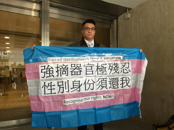 Transgender man, Henry Tse displays a banner outside a local court in Hong Kong Friday, Feb. 1, 2019. Hong Kong's High Court has refused to allow three transgender men, including Tse, to be recognised as males on their official identity cards because they have not undergone full sex-change operations. (Apple Daily via AP)