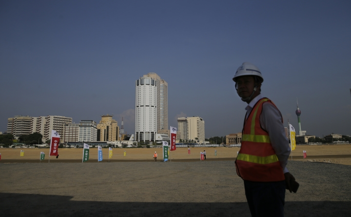 FILE - In this Jan. 2, 2018 file photo, a Chinese construction worker stands on land that was reclaimed from the Indian Ocean for the Colombo Port City project, initiated as part of China's ambitious One Belt One Road initiative, in Colombo, Sri Lanka. Sri Lanka's Finance Ministry spokesman M.R. Hasan said Saturday, Feb. 2, 2019, that he's waiting to hear whether terms of a $1 billion loan from China to construct a highway linking the capital Colombo to the hilly resort city of Kandy for the highway project have been approved. President Maithripala Sirisena's government had criticized the previous administration of strongman Mahinda Rajapaksa for leading the country into a Chinese debt trap. However, the government has turned to China to help relieve economic pressures. (AP Photo/Eranga Jayawardena, File)