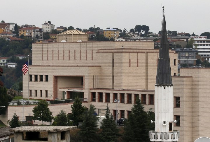 FILE - In this Tuesday, Aug. 11, 2015 file photo, a mosque's minaret is seen backdropped by the United States consulate building in Istanbul. Metin Topuz, a translator and fixer for the Drug Enforcement Agency, working at the consulate, is set to go on trial in March on charges of espionage and attempting to overthrow the Turkish government, a court decided Friday, Feb. 1, 2019. Topuz, has been in custody since October 2017. (AP Photo/Emrah Gurel, FILE)