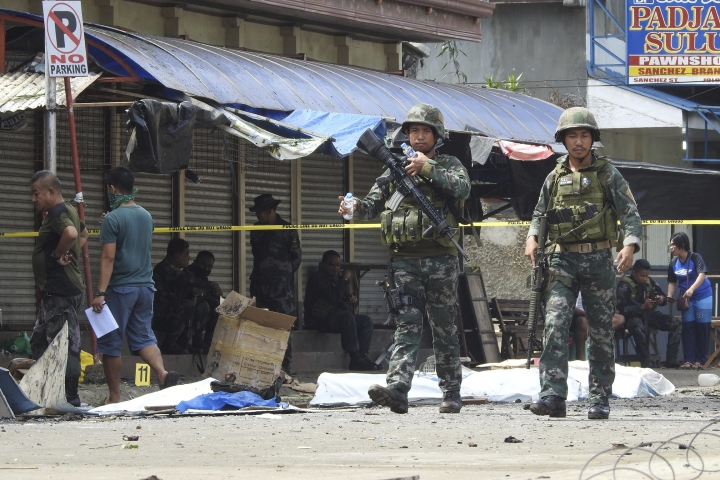 Soldiers attend the scene after two bombs exploded outside a Roman Catholic cathedral in Jolo, the capital of Sulu province in southern Philippines, Sunday, Jan. 27, 2019. Two bombs minutes apart tore through a Roman Catholic cathedral on a southern Philippine island where Muslim militants are active, killing at least 20 people and wounding more than 80 others during a Sunday Mass, officials said. (AP Photo/Nickee Butlangan)