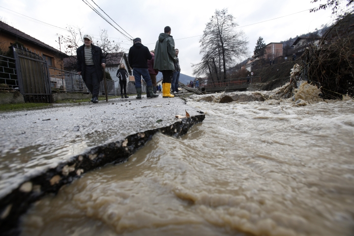 Bosnian people observe damage after flooding in the town of Zenica, Bosnia, Sunday, Feb. 3, 2019. Sudden high temperatures and torrential rain have caused havoc in many parts of Bosnia, with widespread flooding of residential areas. (AP Photo/Amel Emric)