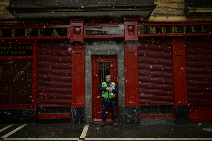 A lottery seller stands on a street as the snow falls, in Pamplona, northern Spain, Sunday, Feb. 3, 2019. Extreme low temperatures with heavy snow have affected the northern part of Spain. (AP Photo/Alvaro Barrientos)
