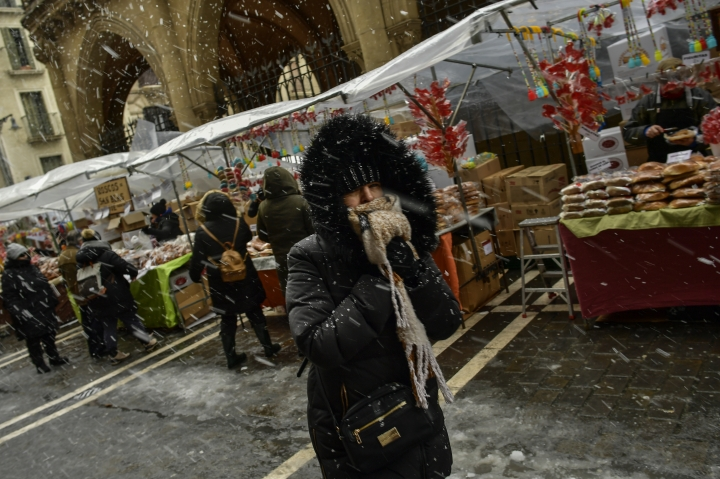 A woman shelters from the snow and strong wind while walking by stands selling sweets during the Saint Blas blessing, in Pamplona, northern Spain, Sunday, Feb. 3, 2019. Extreme low temperatures with heavy snow have affected the northern part of Spain. (AP Photo/Alvaro Barrientos)
