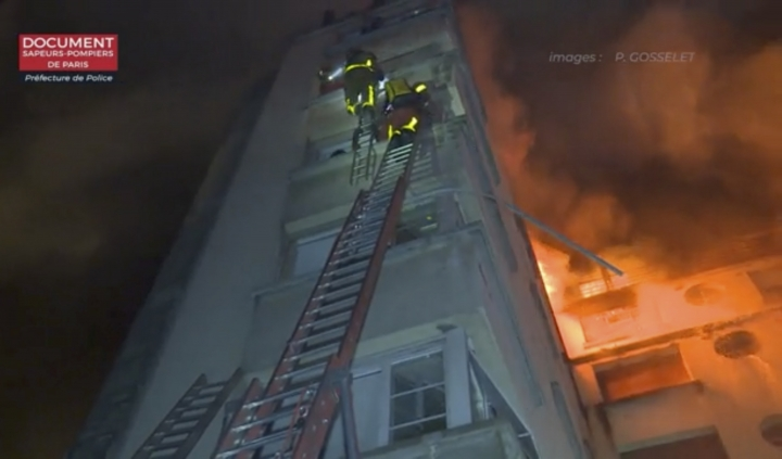 In this image taken from video released by the Paris Fire Dept., firemen climb ladders to the top floors of an apartment building on fire, Tuesday, Feb. 5, 2019, in Paris, France. A fire in a Paris apartment building has killed a number of people and sent residents fleeing to the roof or climbing out windows to escape. (Paris Fire Dept. via AP)