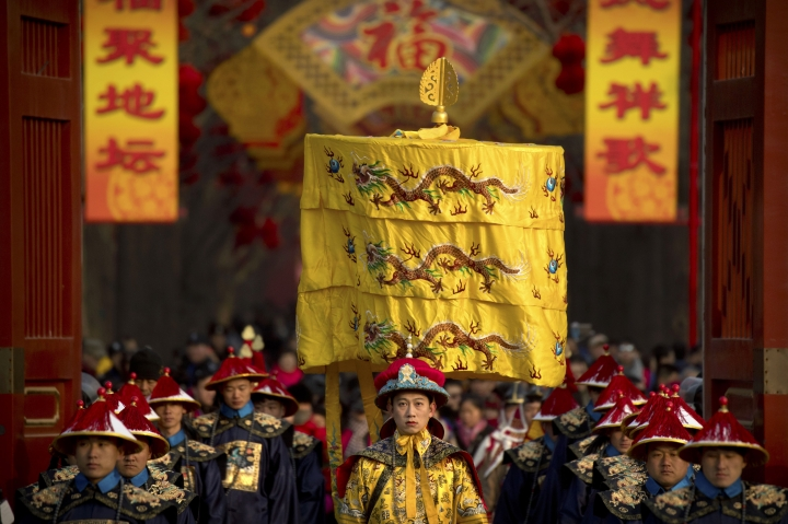 A performer dressed as an emperor, center, participates in a Qing Dynasty ceremony in which emperors prayed for good harvest and fortune at a temple fair in Ditan Park in Beijing, Tuesday, Feb. 5, 2019. Chinese people are celebrating the first day of the Lunar New Year on Tuesday, the Year of the Pig on the Chinese zodiac. (AP Photo/Mark Schiefelbein)