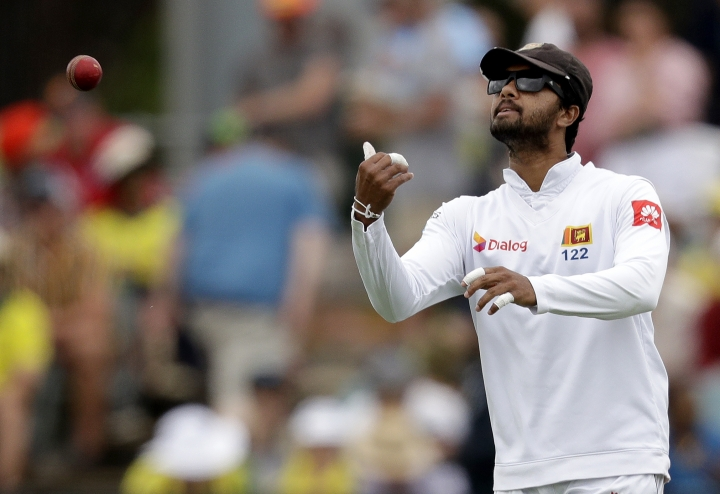 Sri Lanka's Dinesh Chandimal passes the ball to his bowler during their cricket test match against Australia in Canberra, Friday, Feb. 1, 2019. (AP Photo/Rick Rycroft)