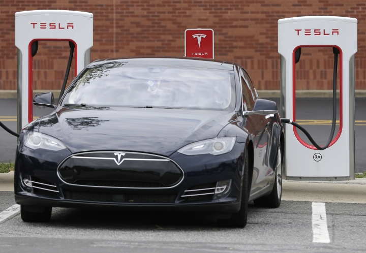 FILE- In this June 24, 2017, file photo, a Telsa Model 3 car recharges at a Tesla charging station at Cochran Commons shopping center in Charlotte, N.C. esla has cut $1,100 from the base price of its Model 3 car designed for the mass market. The electric car company now says on its website that the car starts at $42,900, still short of the target base price of $35,000. For $42,900 buyers will get a rear-wheel-drive Model 3 in black with Tesla's lower-range battery that goes 264 miles per charge. (AP Photo/Chuck Burton)