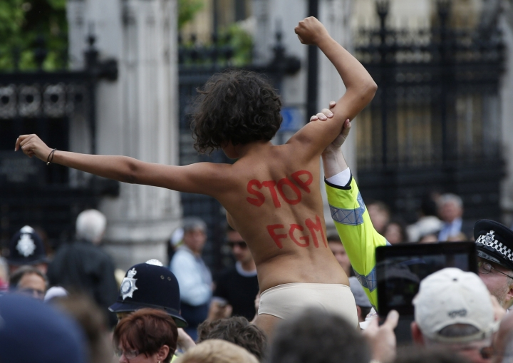 FILE - In this file photo dated Monday, July 7, 2014, a FEMEN activist shouts slogans against female genital mutilation (FGM) during a protest opposite the Houses of Parliament in London. Wednesday Feb. 6, 2019, is the International Day of Zero Tolerance for FGM and many organizations, led by the United Nations, are reaffirming their commitment to end what has been called a violation of human rights. (AP Photo/Lefteris Pitarakis, File)
