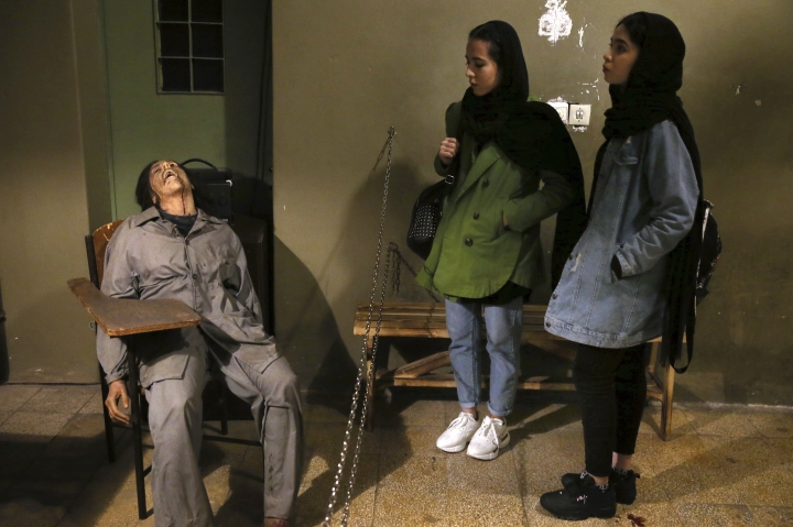 In this Monday, Jan. 7, 2019 photo, women look at an exhibition at a former prison run by the pre-revolution intelligence service, SAVAK, now a museum, where a wax mannequin of a tortured female prisoner is on display, in downtown Tehran, Iran. As Iran marks the 40th anniversary of its Islamic Revolution and the overthrow of the shah, those who suffered torture at the hands of the police and dreaded SAVAK still bear the scars. U.N. investigators and rights group say that even today, Iran tortures and arbitrarily detains prisoners. (AP Photo/Ebrahim Noroozi)