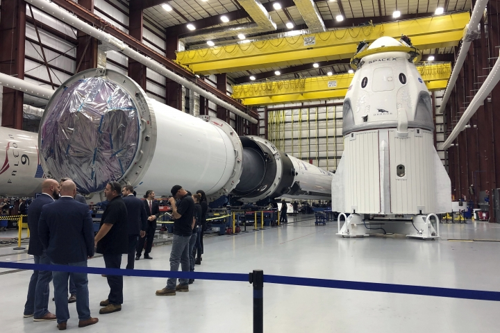 FILE - In this Tuesday, Dec. 18, 2018 file photo, SpaceX's Dragon capsule, right, sits in a SpaceX hangar in Cape Canaveral, Fla. On Wednesday, Feb. 6, 2019, officials set March 2 as the latest launch date for an unmanned test. If the demo goes well, two NASA astronauts will take a test flight in July. (AP Photo/Marcia Dunn)