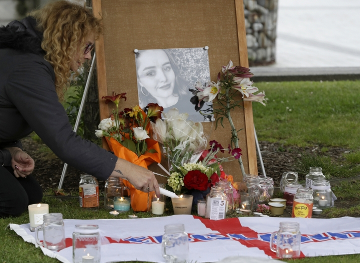 FILE - In this Dec. 12, 2018, file photo, a woman lights candles during a candlelight vigil for murdered British tourist Grace Millane at Cathedral Square in Christchurch, New Zealand. The man accused of murdering Millane will continue to keep his name secret while a judge decides whether he can be publicly identified. The 27-year-old man appeared Thursday, Feb. 7, 2019, in Auckland's High Court. (AP Photo/Mark Baker, File)