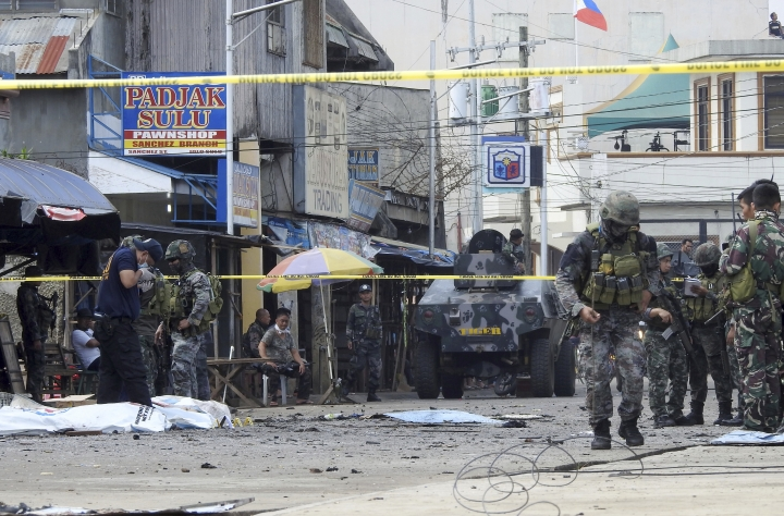 FILE - In this Jan. 27, 2019, file photo, police investigators and soldiers attend the scene after two bombs exploded outside a Roman Catholic cathedral in Jolo, the capital of Sulu province in southern Philippines. Abu Sayyaf commander Hatib Hajan Sawadjaan accused of plotting the attack in the cathedral may be harboring a foreign would-be suicide bomber in his jungle base, a senior official said Thursday, Feb. 7, 2019. Sawadjaan's goal was to assert his new role as Islamic State group leader in the southern Philippines. (AP Photo/Nickee Butlangan, File)