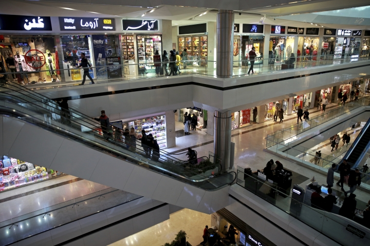 In this Wednesday, Feb. 6, 2019 photo, people walk through the Kourosh shopping mall, in Tehran, Iran. The economy faces multiple struggles as the country marks the 40th anniversary of the Islamic Revolution. Inflation continues to rise as its currency depreciates and university graduates are unable to find jobs. Some of the challenges stem from the re-imposition of U.S. sanctions while other problems date back to the time of the revolution. (AP Photo/Vahid Salemi)