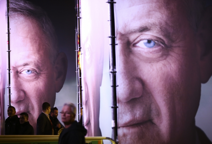 """FILE - In this Jan. 29, 2019, file photo, people walk by posters of retired Israeli military chief Benny Gantz before the official launch of his election campaign for the April 2019 elections, in Tel Aviv. Gantz has burst onto the Israeli political scene as the great hope of the country's shrinking """"peace camp"""" with a message that is anything but dovish. The retired general, who hopes to topple Prime Minister Benjamin Netanyahu in April 9 elections, talks tough. In today's Israel, his ready-to-rumble rhetoric appears to be the only way to topple the long-serving Netanyahu. (AP Photo/Oded Balilty, File)"""