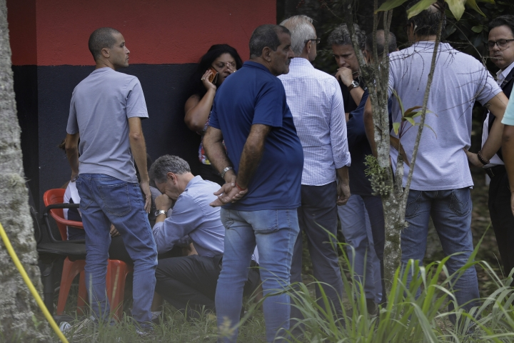 In this photo taken through the gate of the Flamengo soccer club training complex, Brazil's Flamengo president, Rodrigo Landim, second from left, bottom, comforts relatives of the victims inside the facility after a deadly fire at the soccer club in Rio de Janeiro, Brazil, Friday, Feb. 8, 2019. A fire tore through the sleeping quarters of the Flamengo soccer club development league, one of Brazil's most popular professional soccer clubs, killing several people who were most likely players and injuring others, authorities said. (AP Photo/Leo Correa)