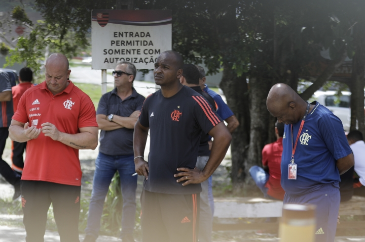 In this photo taken through the gate of the Flamengo soccer club training complex, team employees stand and wait after a deadly fire at the soccer club in Rio de Janeiro, Brazil, Friday, Feb. 8, 2019. A fire tore through the sleeping quarters of the Flamengo soccer club development league, one of Brazil's most popular professional soccer clubs, killing several people who were most likely players and injuring others, authorities said. (AP Photo/Leo Correa)