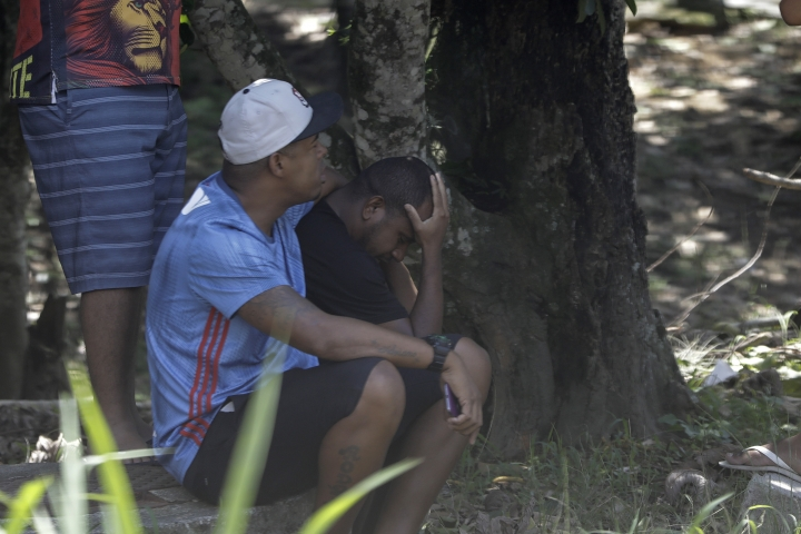 In this photo taken through the gate of the Flamengo soccer club training complex, relatives cry as they sit inside the facility after a deadly fire at the soccer club in Rio de Janeiro, Brazil, Friday, Feb. 8, 2019. A fire tore through the sleeping quarters of the Flamengo soccer club development league, one of Brazil's most popular professional soccer clubs, killing several people who were most likely players and injuring others, authorities said. (AP Photo/Leo Correa)