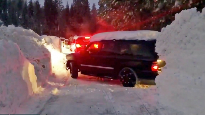 This Wednesday, Feb. 6, 2019 photo from video by Joel Keeler shows vehicles driving through canyons plowed through snow drifts that overshadow them at snowed-in Montecito Sequoia Lodge in Kings Canyon National Park in California's Sierra Nevada. More than 120 visitors and staff who became snowbound in the Sierra Nevada resort for five days have been freed. The U.S. Forest Service says snow trapped the guests and staff at the lodge starting Sunday following a storm. They couldn't get out until Thursday night, Feb. 7, 2019. (Joel Keeler via AP)