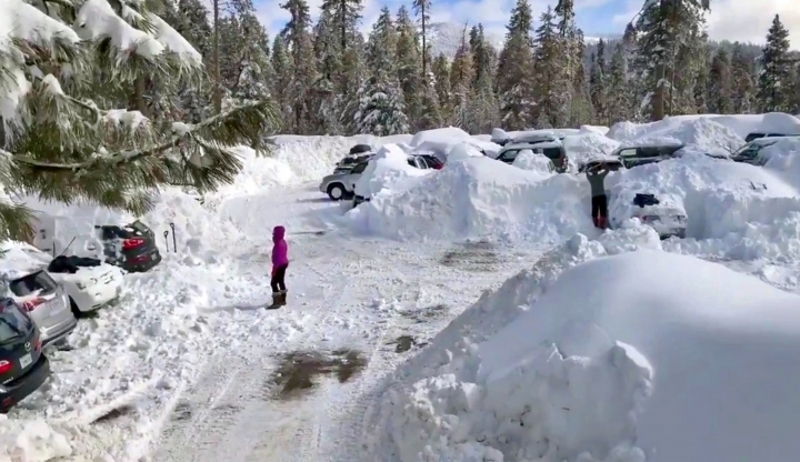 This Wednesday,, Feb. 6, 2019 photo from video by Joel Keeler shows people attempting to clear cars buried in the parking lot of the showed-in Montecito Sequoia Lodge in Kings Canyon National Park in California's Sierra Nevada. More than 120 visitors and staff who became snowbound in the Sierra Nevada resort for five days have been freed. The U.S. Forest Service says snow trapped the guests and staff at the lodge starting Sunday following a storm. They couldn't get out until Thursday night, Feb. 7, 2019. (Joel Keeler via AP)