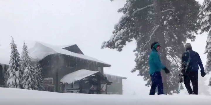This Tuesday, Feb. 5, 2019 photo from video by Joel Keeler shows people approaching the showed-in Montecito Sequoia Lodge in Kings Canyon National Park in California's Sierra Nevada. More than 120 visitors and staff who became snowbound in the Sierra Nevada resort for five days have been freed. The U.S. Forest Service says snow trapped the guests and staff at the lodge starting Sunday following a storm. They couldn't get out until Thursday night, Feb. 7, 2019. (Joel Keeler via AP)