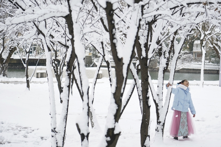 In this Friday, Feb. 8, 2019, photo released by China's Xinhua News Agency, a girl plays at the lakeside of Baijia Lake in Nanjing, capital of east China's Jiangsu Province. Blizzards in Tibetan areas of western China have left thousands of head of livestock dead and roads covered in up to 45 centimeters (18 inches) of snow, state media reported Saturday. (Ji Chunpeng/Xinhua via AP)