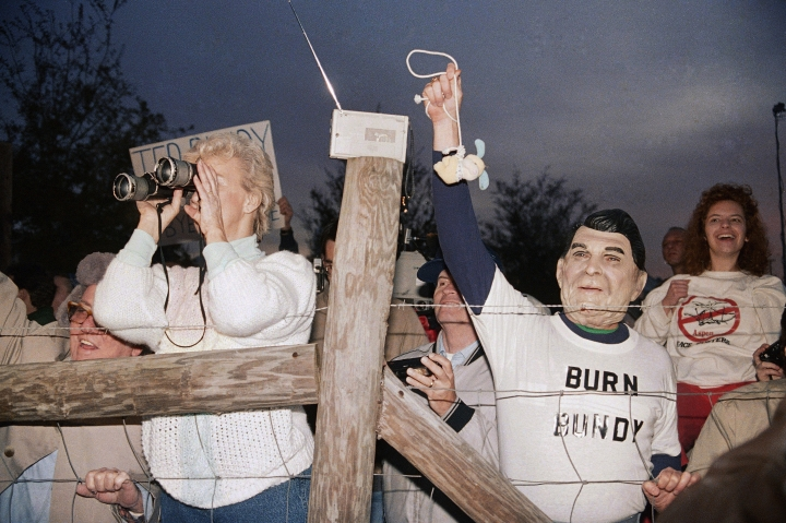 FILE - In this Jan. 25, 1989 file photo, a toy bunny is hung in effigy by Jerry Jackson of Atlanta Ga., wearing a Ronald Reagan mask, as a crowd celebrates the execution of Ted Bundy at sunrise in Starke, Fla. (AP Photo/Mark Foley)