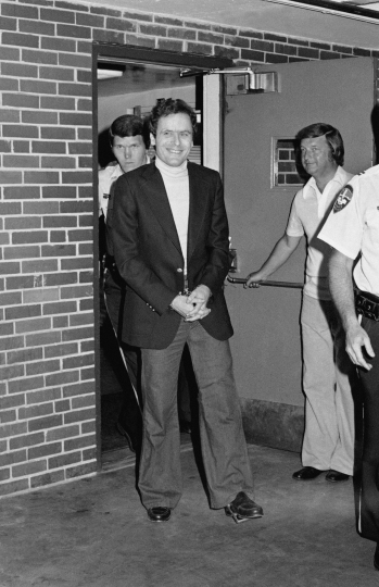 FILE - In this June 13, 1977 file photo, Ted Bundy appears in cuffs after being recaptured just outside of Aspen City limits. He was pulled over by the sheriff's department for driving erratically. The officers did not know it was him until they approached the car. He offered no resistance. (AP Photo)