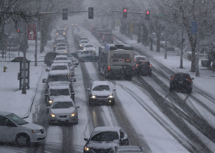 Cars and a bus make their way in the snow on Capitol Way, Friday, Feb. 8, 2019, in Olympia, Wash. A much-anticipated winter storm hit Washington state Friday, and many businesses, schools, and offices closed early so workers could get home. State and local officials urged people to stay off the roads as traffic slowed to a standstill in some places because of the snow. (AP Photo/Ted S. Warren)